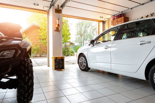 Home suburban countryside modern car and ATV double garage interior with wooden shelf, tools and equipment stuff storage warehouse indoors against sun light. Vehicle parked house parking background