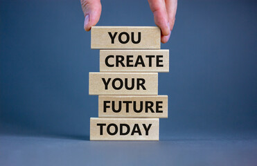 You create your future today symbol. Concept words 'You create your future today' on wooden blocks on a beautiful grey background. Businessman hand. Business, motivational and create future concept.