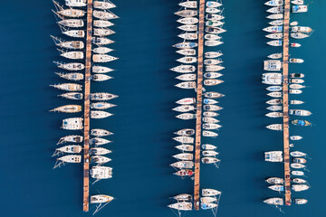 Fototapeta Aerial view of the yacht club. Aerial top-down view of docked sailboats. Top down view of yachts