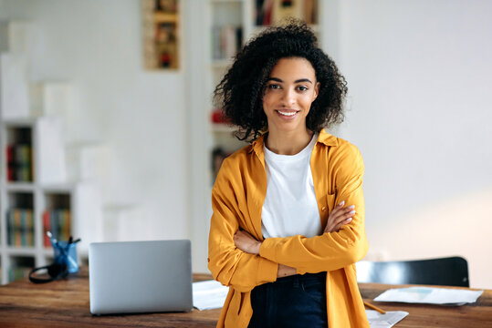 Portrait of a pretty African American girl. Confident stylish young african american woman with curly hair, stands near the desktop with crossed arms, looks at the camera, smiles friendly