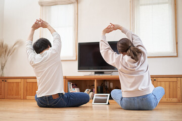 Fototapeta 自宅のリビングでストレッチをするアジア人の夫婦 obraz