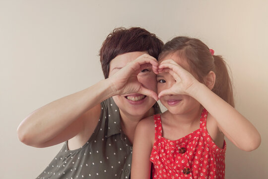 Asian mother and daugther girl making heart shape gesture with hands over eyes , Happy volunteer ,donation and charity, family love, heart health insurance , mental health concept