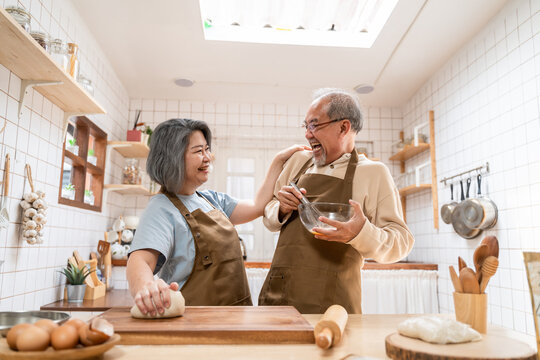 Asian senior couple helping each other for homemade bakery cooking.