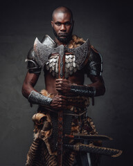 Fototapeta Medieval black skinned warrior with axes staring at camera in dark background