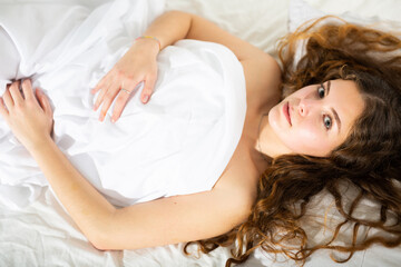Fototapeta Portrait of young brown-haired girl covered with white bedsheet enjoying lying in comfy bed looking at camera..