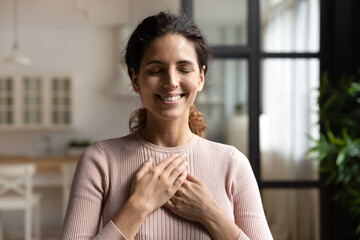 Obraz Thank you my God. Happy peaceful millennial hispanic lady stand alone with closed eyes keep hands close to heart hope pray in mind. Emotional young woman express deep gratitude impressed by good deed - fototapety do salonu