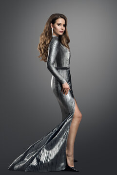Fashion Model in luxury Silver long Dress. Elegant Woman with Curly Long Hair Hairstyle in Evening Gown with Slit showing Leg over dark Gray Studio Background
