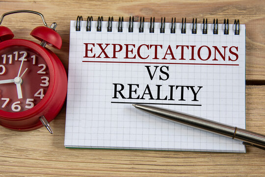 EXPECTATIONS VS REALITY - words in a notebook on a wooden background with a pen and an alarm clock