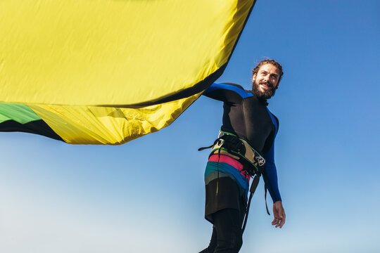 Young man professional surfer standing on the sandy beach with his kite