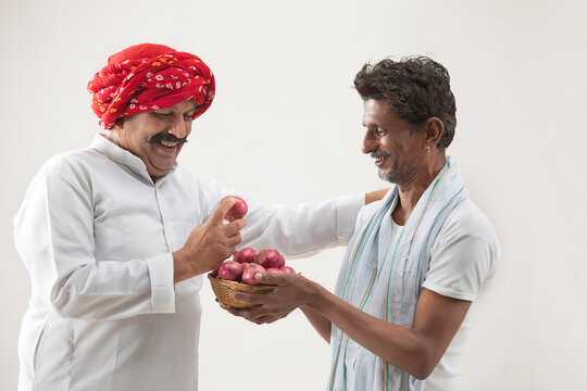 A FARMER HOLDING A BASKET OF ONIONS WHILE VILLAGER LOOKS AT IT