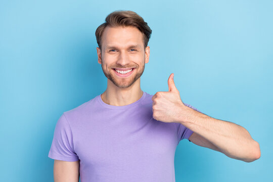 Photo of satisfied cheerful man beaming smile show thumb up look camera isolated on blue color background