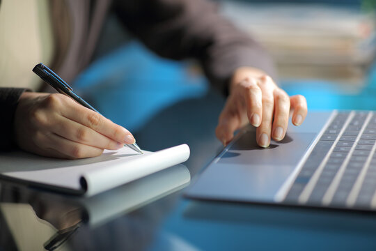 Woman hand taking notes on notebook using laptop in the night