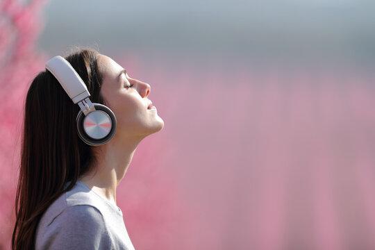 Woman meditating listening audio on headphones in a field
