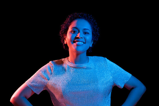 leisure, clubbing and nightlife concept - smiling young african american woman over ultraviolet neon lights on black background