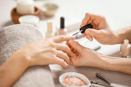 Woman applying nail polish at nail salon
