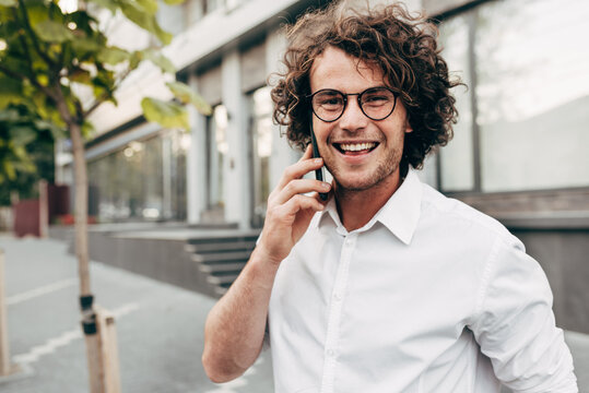 Outdoor image of a young man with curly hair smiling while talking with his friend on a mobile phone. A happy curly male wearing a white shirt has a joyful expression during speaking on a cellphone.