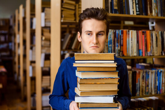 Male student with negative and bored mimic on his face holding a big stack of books in the library. Concept of hard education, learning