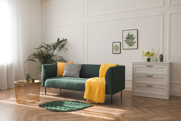 Stylish living room interior with comfortable green sofa