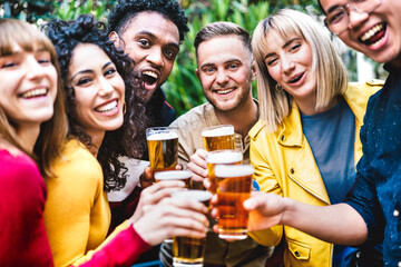 Fototapeta Happy friends toasting beer at brewery bar dehor - Friendship life style concept with young millennial people enjoying time together at open air pub - Warm vivid filter with focus on central guy