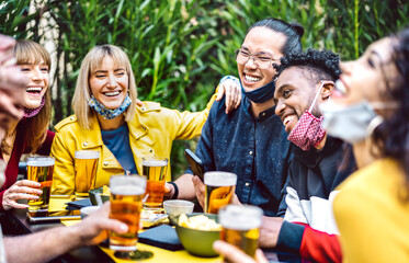 Fototapeta Young people drinking beer with opened face mask - New normal life style concept with millenial friends having fun together on happy hour at brewery garden party - Vivid filter with focus on asian guy