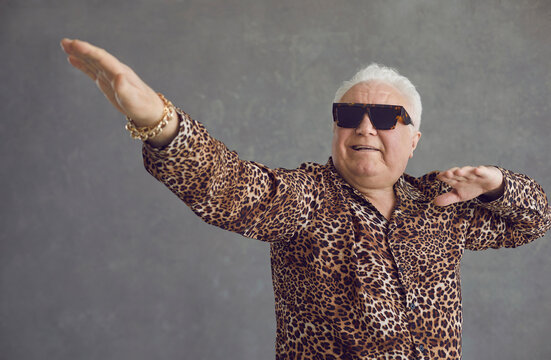 Retired senior man vibing to hype pop music. Portrait of funny rich white haired old grandpa in cool glasses and leopard patterned party shirt flexing, dancing and having fun on gray studio background