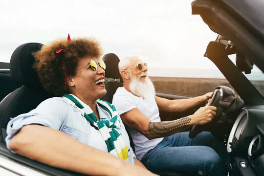 Senior trendy couple inside a convertible car on holiday time - Travel, fashion and joyful elderly concept - Focus on woman face