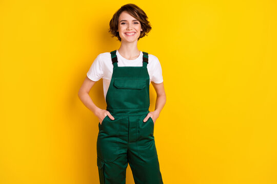 Photo of pretty cheerful girl put arms in pockets toothy smile look camera isolated on yellow color background