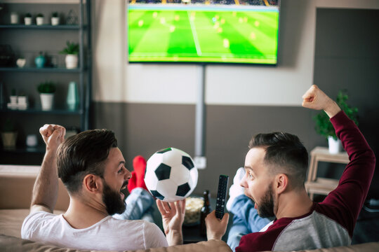 Back view photo of two best friends and fans of football watching some sport match on the TV and drinking beers and eating snacks while cheering for the team on the couch