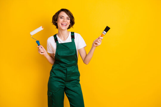 Photo of optimistic nice brown hair lady hold roller brush wear uniform isolated on yellow background