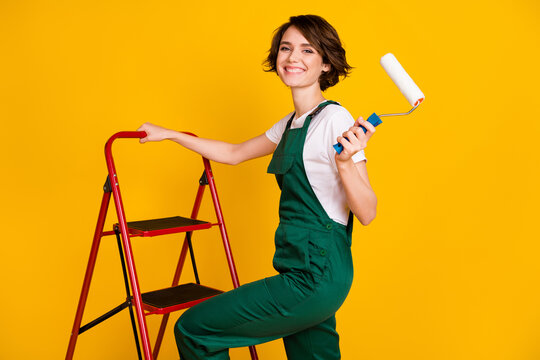 Photo of happy positive smiling girl painter climbing ladder hold roller renovation isolated on yellow color background