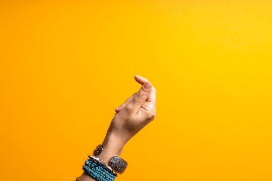 Hand gestures. Click your finger. Women's hand with lots of bracelets, youth fun style.