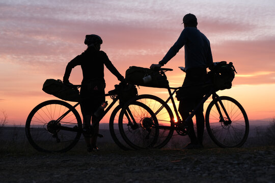 Bike packing cyclists leaning on their packed bikes during springtime sunset