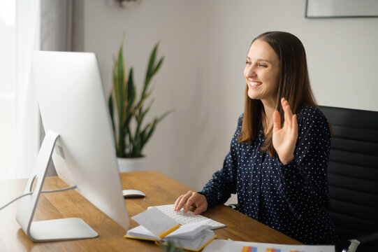 Video conference concept. Young positive businesswoman using computer for video communication with coworkers, colleagues on the distance, female employee holding video meeting, waving into webcam