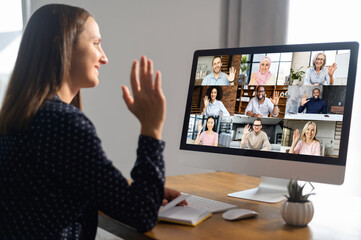 Online video discussion with many people together. Young woman sits in front of laptop with many icons, photo profiles of people on screen. App for video meeting with diverse team