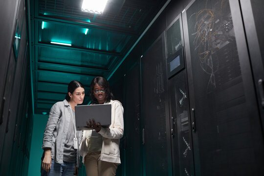 Waist up portrait of two female IT engineers setting up server network via laptop while working in data center, copy space