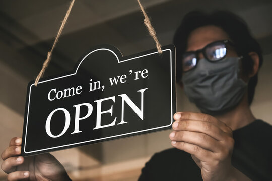 The state allows retail stores or restaurants and businesses to reopen after coronavirus restrictions. man with face mask turning a sign on a door shop. economy starts running after being on lockdown.