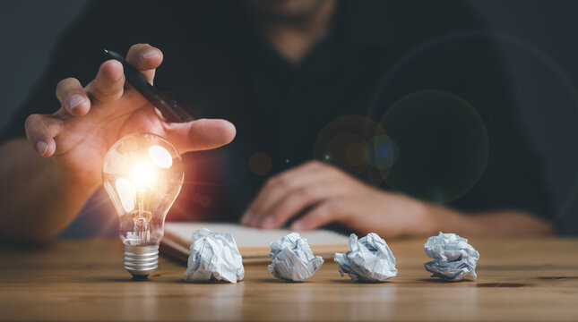 new idea and light bulbs concept with man hand touching light bulb and four crumpled office paper,.businessman show new ideas with innovative technology and creativity.