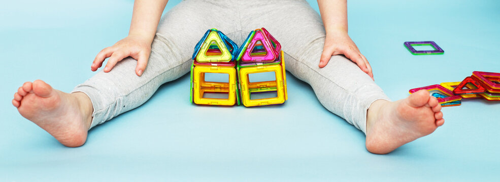 Little girl playing with colorful magnetic constructor toy on blue background. child built a house. banner