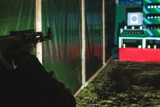 Silhouette of a man hands with a machine gun shoot at targets in a dash on nature in a tent, selective focus