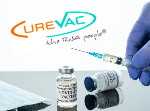 Morgantown, WV - 19 April 2021: Small bottle of coronavirus vaccine with syringe with background of CureVac logo