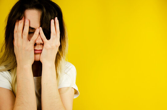 Girl on a yellow background. The woman covers her face with her hands. Fear. The woman is in fear. The girl hides her face with her hands on a yellow background. Emotions. Is under pressure.