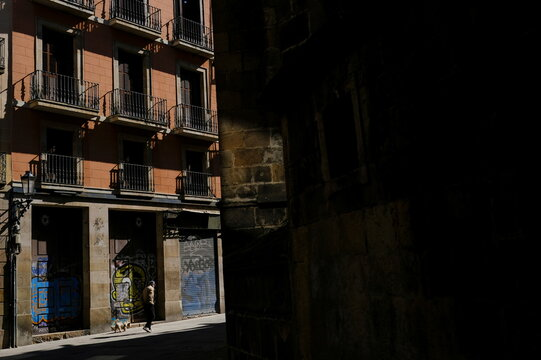 A man wearing a protective face mask walks with his pet dog on a street, in Barcelona