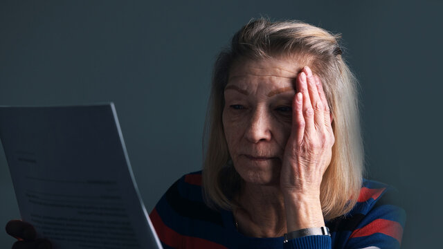 Desperate elderly woman reading eviction notice. High quality photo