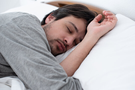Young man sleeping peacefully lying in bed