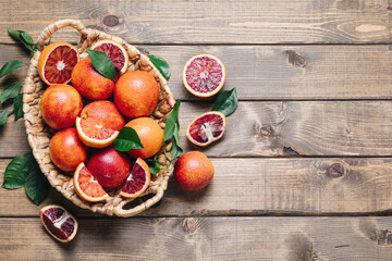 Whole and sliced blood oranges in a basket on wooden table background. Flat lay, top view, copy...