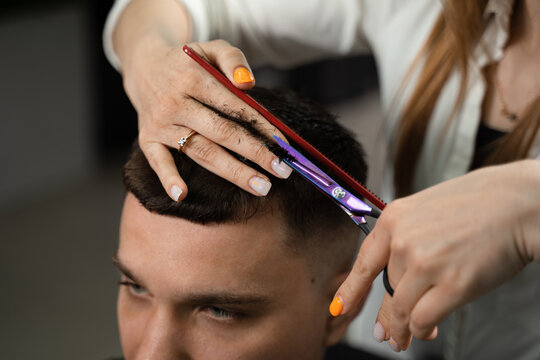 Haircut and styling in barbershop for handsome man. Woman making hairstyle using scissors.