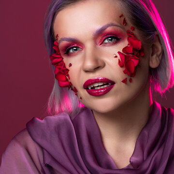 Glamorous vampire look with bright pink eye shadow and flower petals on the skin
