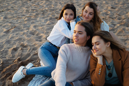 Group of young women in casual outfit on the beach, enjoying the sunset.