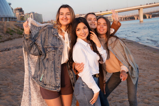 Group of friends having fun on the beach, meeting friends. Young women