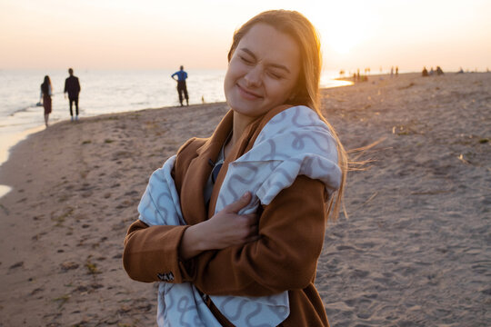 young beautiful woman wrapped up in a warm blanket, warm and cozy on the beach.